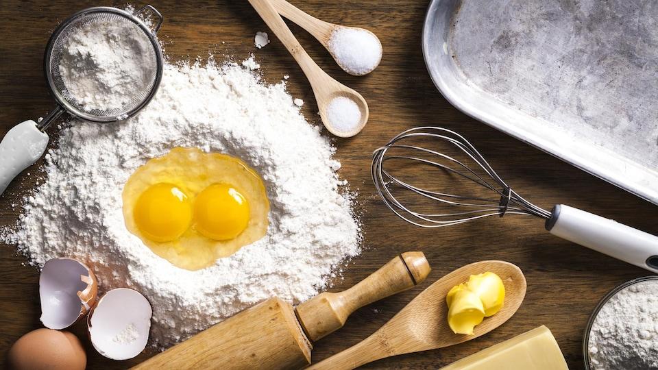 Des œufs et de la farine sont disposés sur un plan de travail.
