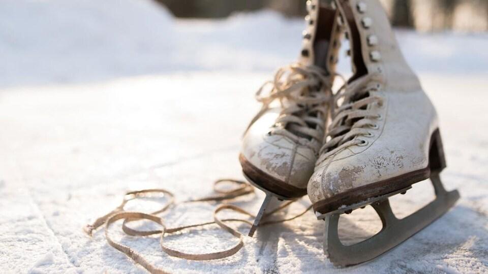 Photo d'une vielle paire de patins à glace sur une patinoire extérieure.