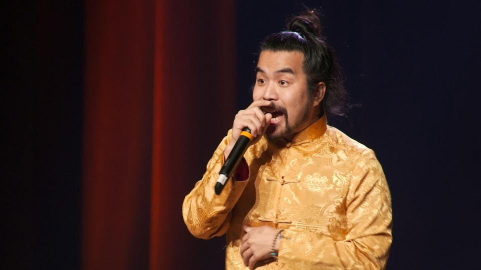 Anto Chan porte une veste chinoise jaune, ses cheveux sont attachés et il a un micro à la main.
