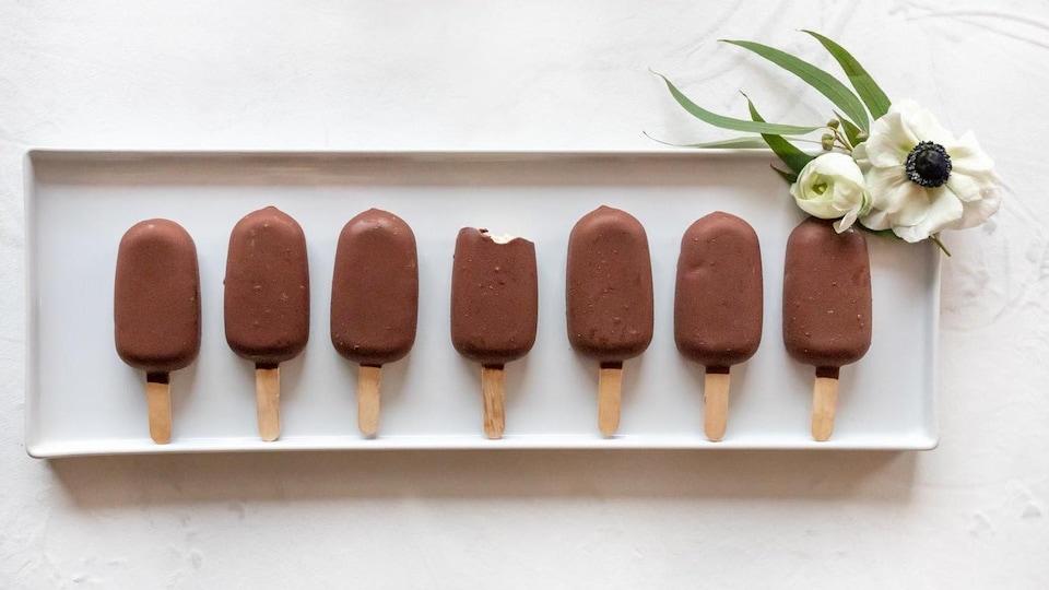Une assiette blanche remplie de desserts glacés trempés dans du chocolat.