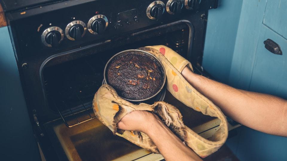 Les mains d'un homme qui retire un gâteau brûlé du four.