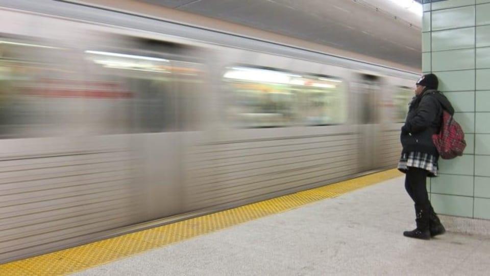 Une femme s'adosse à un mur pendant qu'un métro passe devant elle.