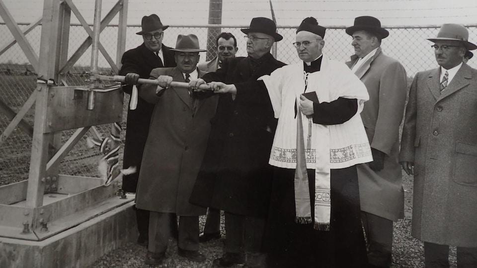 Une photo en noir et blanc montrant six hommes des années 50 en compagnie d'un curé au pied d'un pylône électrique.