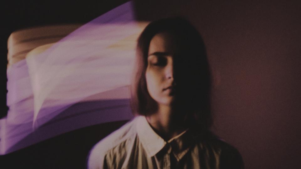 Une jeune femme, les yeux fermés, est entouré de ruban colorés virtuels.