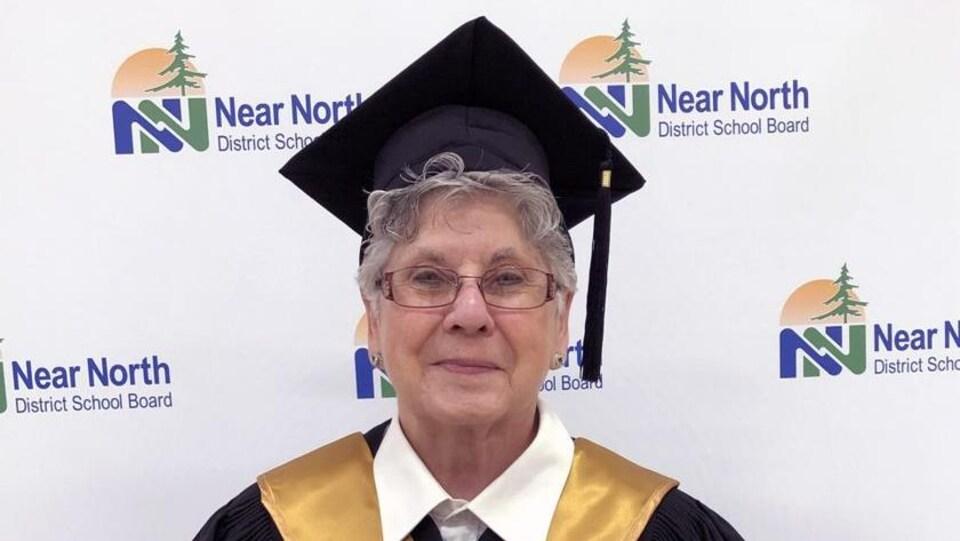 Une dame âgée vêtue d'une toge de finissante tient son diplôme d'études secondaires dans ses mains.