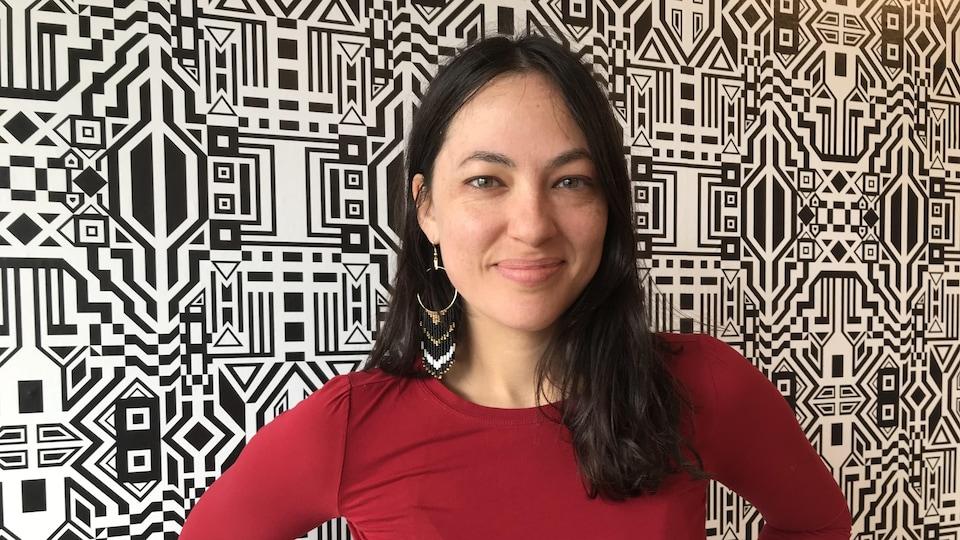 Caroline Monnet devant une murale composée de nombreux motifs.