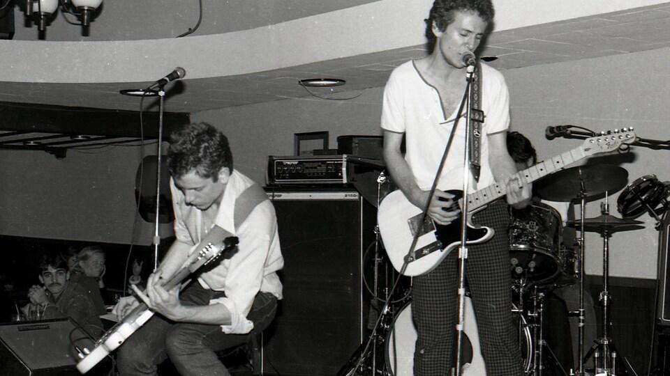 Photo en noir et blanc de deux guitaristes en performance sur une scène devant public.