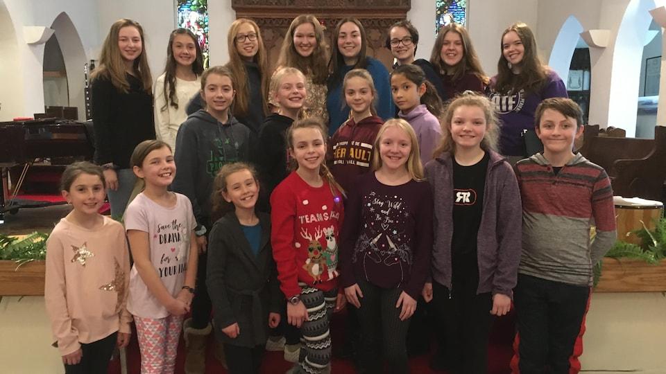 Une vingtaine de jeunes entre 9 et 18 ans qui forment la chorale De tout choeur de Timmins sourient pour la caméra. La chorale communautaire jeunesse De tout choeur est inscrite au concours «Les choeurs du Nord» organisé par ICI Nord de l'Ontario