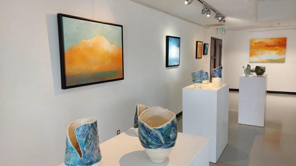 Une galerie d'art où sont accrochés des tableaux de cieux ennuagés; des pots en céramique sont exposés sur des socles