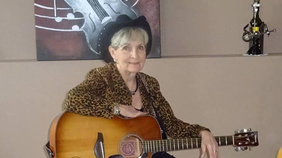 Une femme portant un chapeau de cowboy est assise avec une guitare dans son salon.