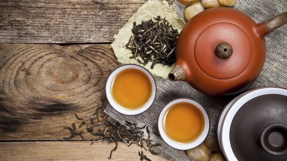 Deux théières, deux tasses de thé et des feuilles de thé sur une surface en bois