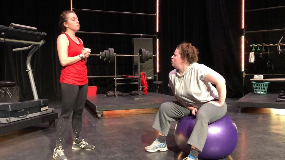 Une entraîneuse surveille une femme qui s'exerce à l'aide d'un ballon d'exercice.