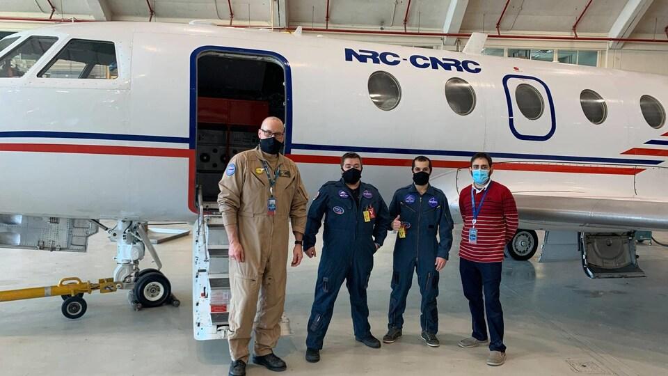Les quatre hommes debout devant un avion de du CNRC.