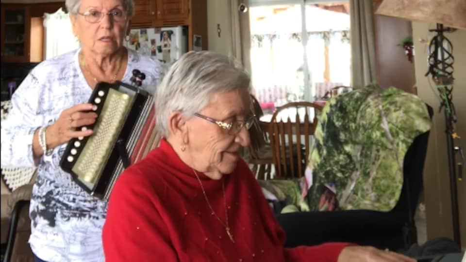 Deux soeurs âgées de 89 et 85 ans regardent la caméra. Jeannette Filion joue de l'accordéon et sa soeur Thérèse l'accompagne au clavier électronique.