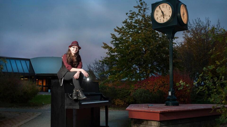 Une femme assise sur un piano, en plein air, au clair-obscur