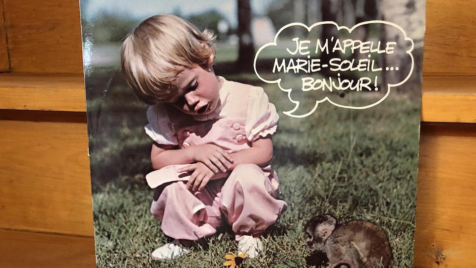 Couverture d'album avec une petite fille vêtue de rose.