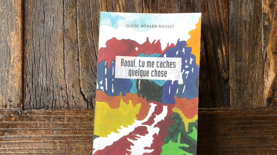 La page couverture d'un roman, placé sur une table de bois.