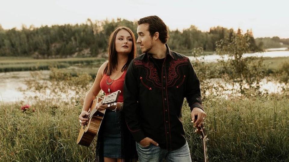 Une jeune femme et un jeune homme en pleine nature avec leurs guitares