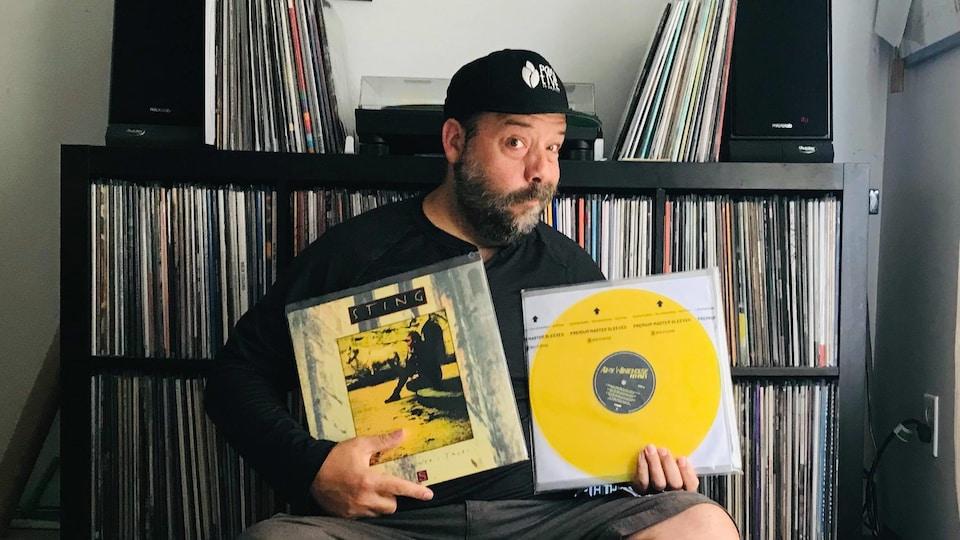 Stef Paquette devant sa collection de vinyles et sa table tournante. Il a un disque de Sting et un disque d'Amy Winehouse entre les mains.