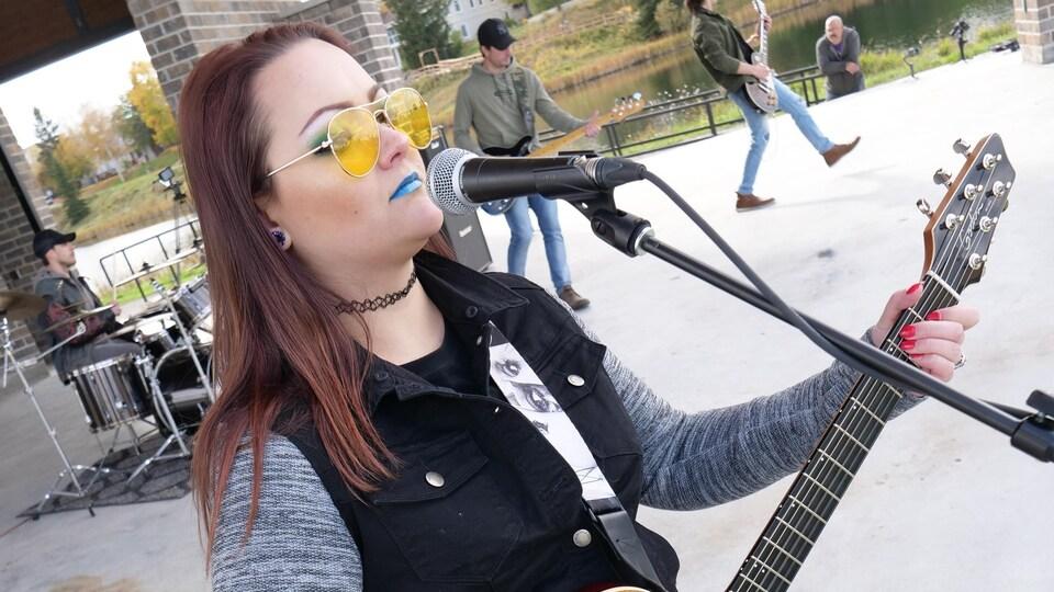 Une jeune femme joue à la guitare près d'une scène en plein air