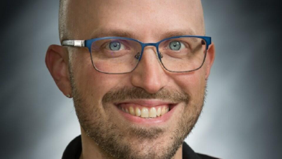 Photo professionnelle du visage souriant de Thierry Croussette. Il porte de lunettes bleues.