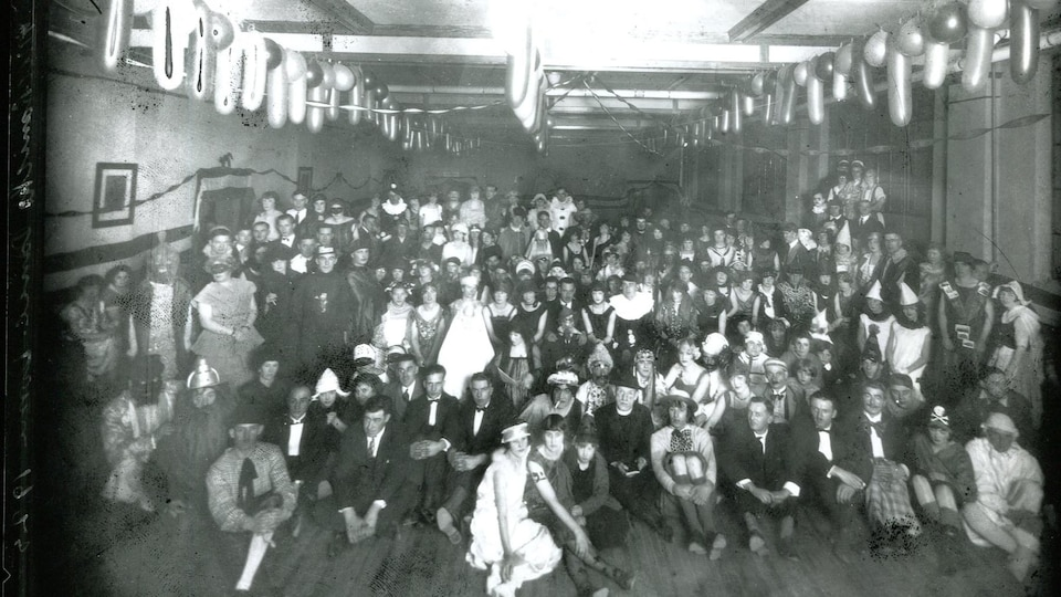 Une photo de groupe prise lors d'un bal masqué au tournant du 20e siècle.