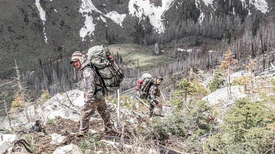 Les deux hommes descendent la montagne avec leur gros sac à dos.