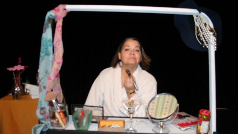 Une comédienne se maquille devant un faux-miroir dans un décor de théâtre.
