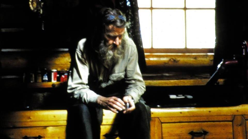 Un homme avec une longue barbe est assis sur un comptoir de cuisine