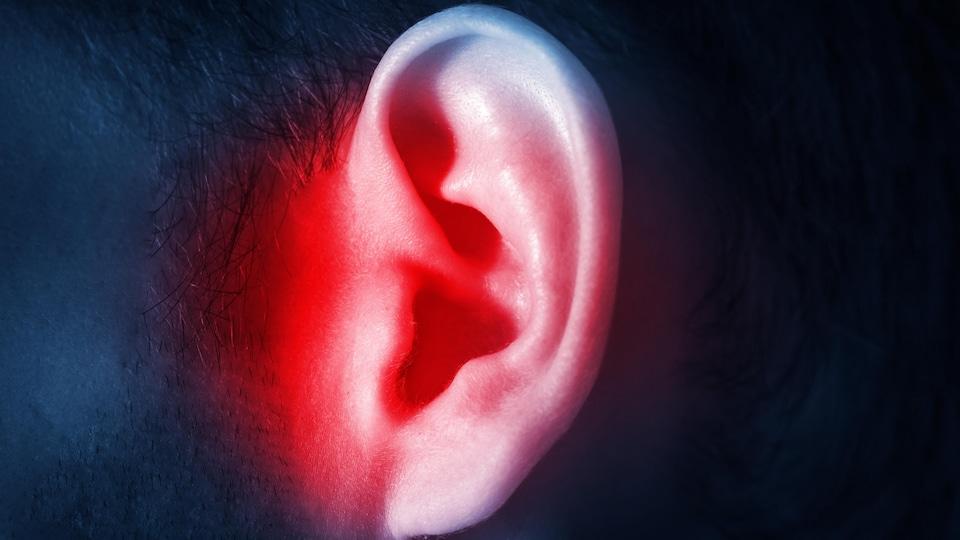 Une oreille d'un homme qui est aux prises avec un acouphène.