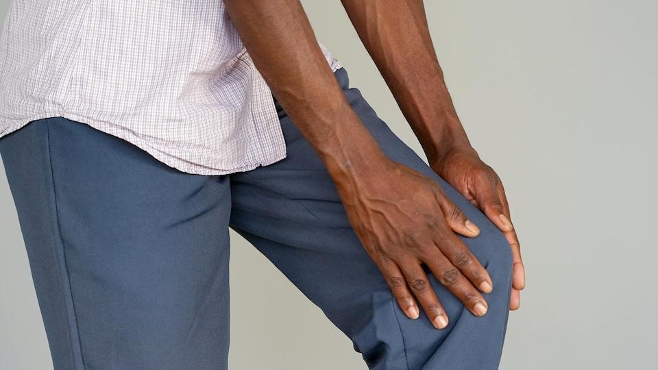 Une personne palpe de ses deux mains son genou gauche.