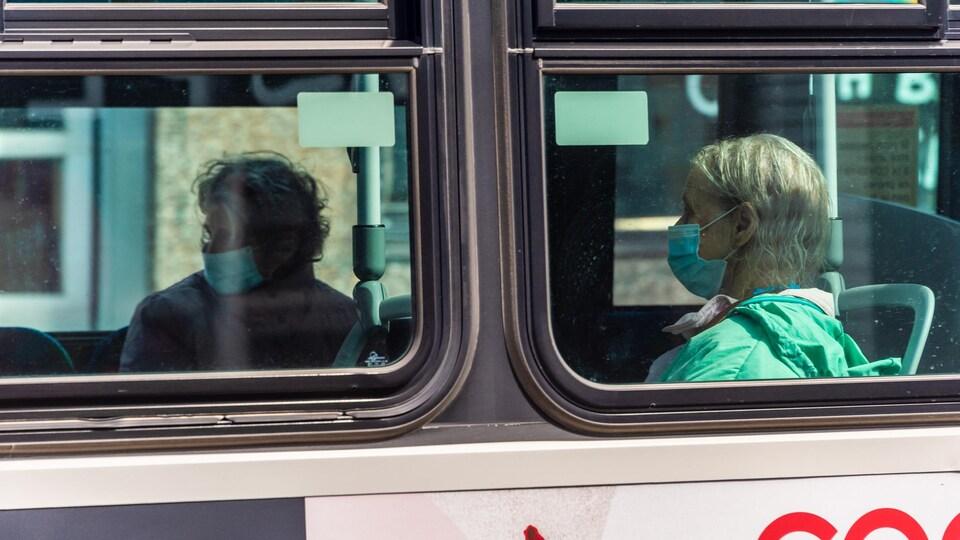 Des personnes sont assises dans un autobus de Montréal.