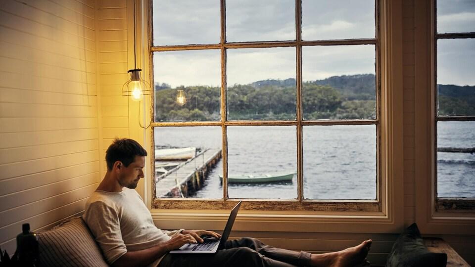un homme travaille devant son ordinateur alors qu'il est dans un chalet.