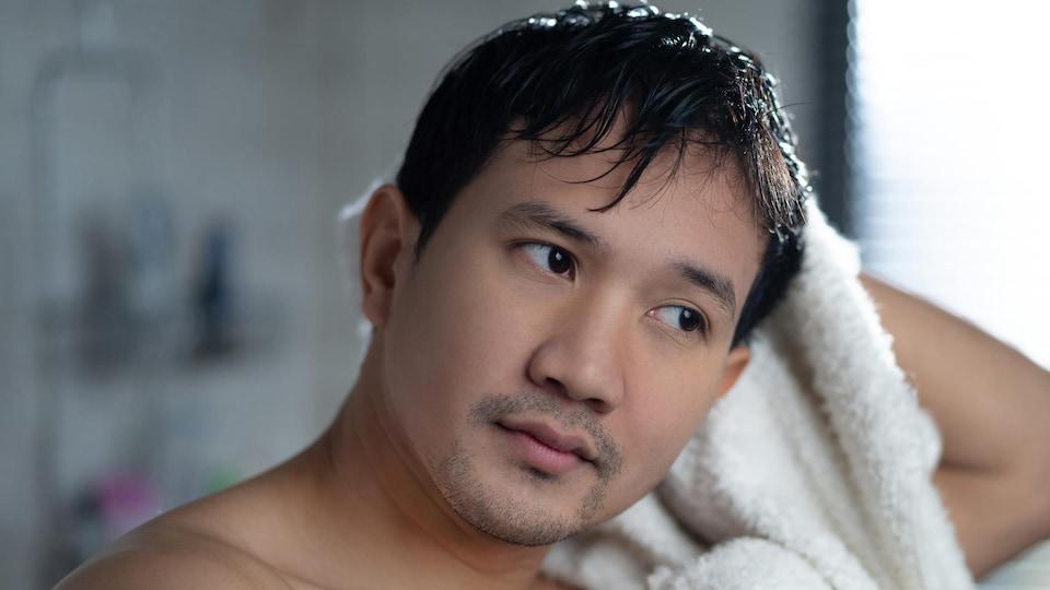 Une personne se sèche les cheveux à l'aide d'une serviette, l'air détendu.