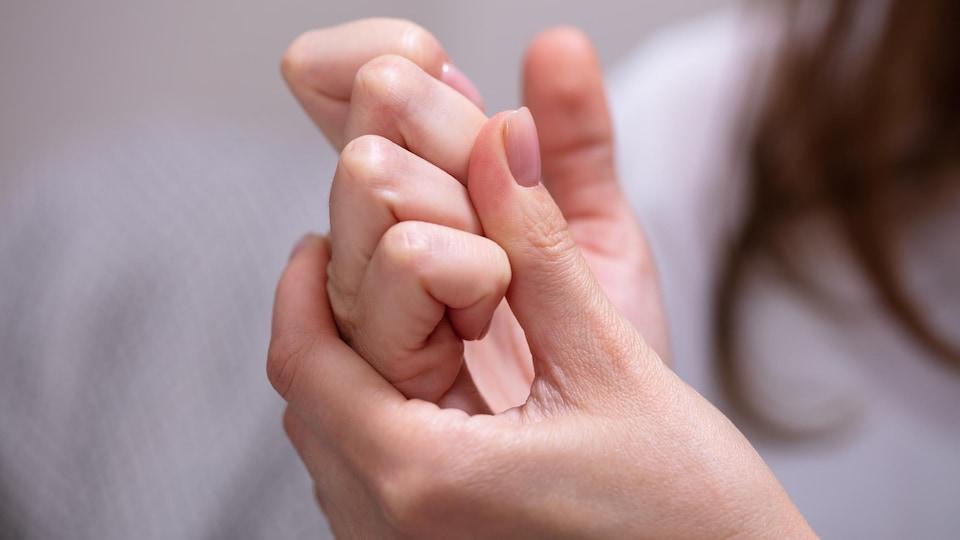 Une femme se fait craquer les doigts de la main droite.