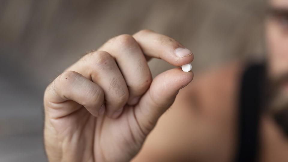 Une personne tient un comprimé dans sa main droite.