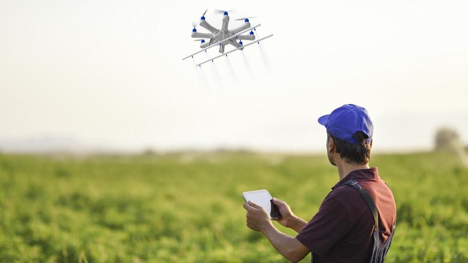 Une personne qui se trouve dans un champ contrôle un drone à distance.