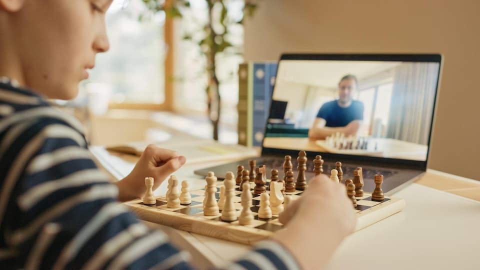 Un garçon joue aux échecs avec une autre personne en ligne.