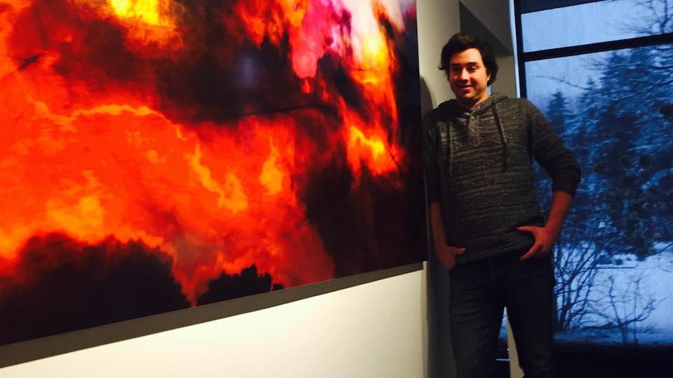 Étienne Saint-Amant se tient à côté d'une de ses œuvres.