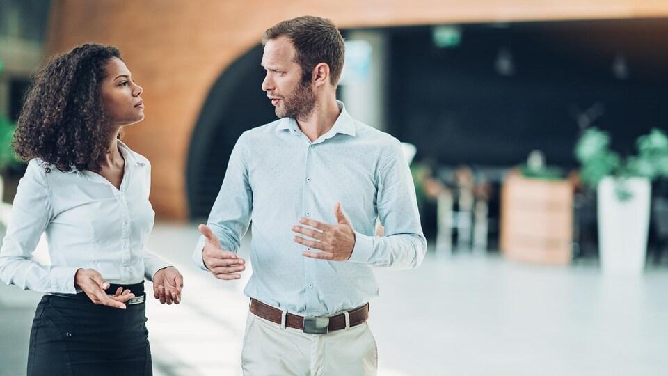 Une femme et un homme issus du milieu du travail discutent fermement dans le lobby d'un hôtel.