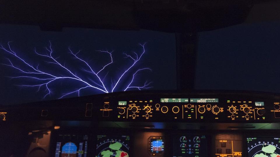 Un feu de Saint-Elme apparaît à l'extérieur d'un avion, en pleine nuit.