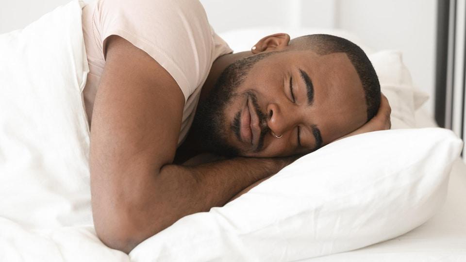 Un homme dort paisiblement dans son lit.