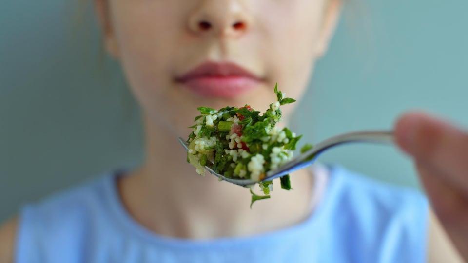 Une femme s'apprête à prendre une bouchée de salade.