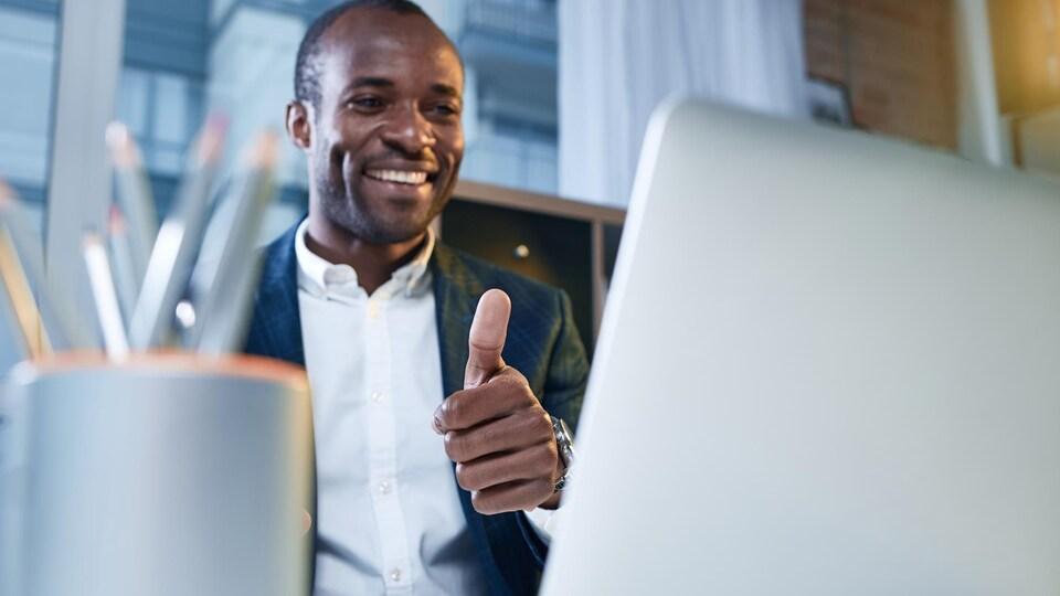 Une personne sourit et lève son pouce de la main gauche devant son écran d'ordinateur.