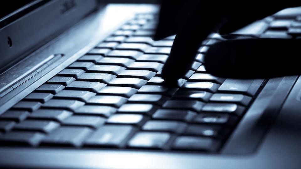 Une personne tape une lettre sur un clavier d'ordinateur.