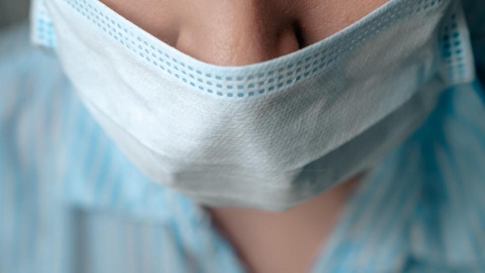 Une personne porte un masque pour se protéger de la COVID-19.