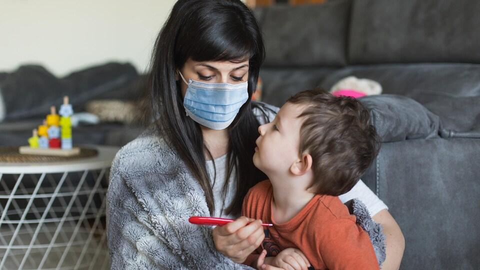 Une mère porte un masque et prend la température de son fils.