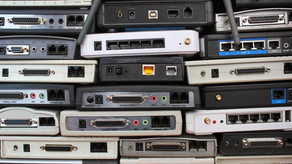Des modems et des routeurs usagés sont empilés les uns sur les autres.