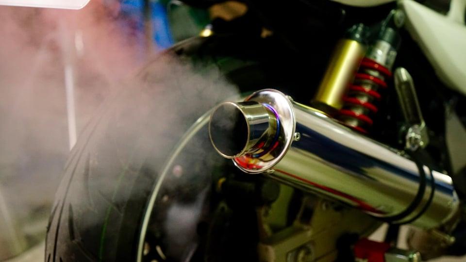 Une motocyclette crache des émissions polluantes de son tuyau d'échappement.