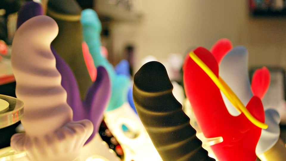 Des jouets sexuels, dont des vibrateurs, sont exposés dans le présentoir d'un magasin.